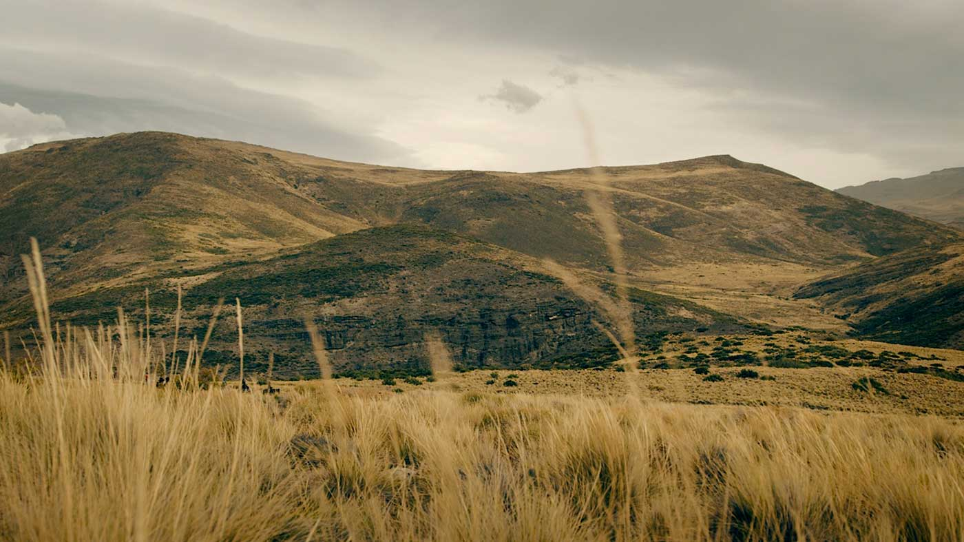 Under ominous skies, the riders cross fields of bunch grass in the Andes foothills.