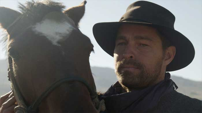 Close-up portrait of Brett with his horse.