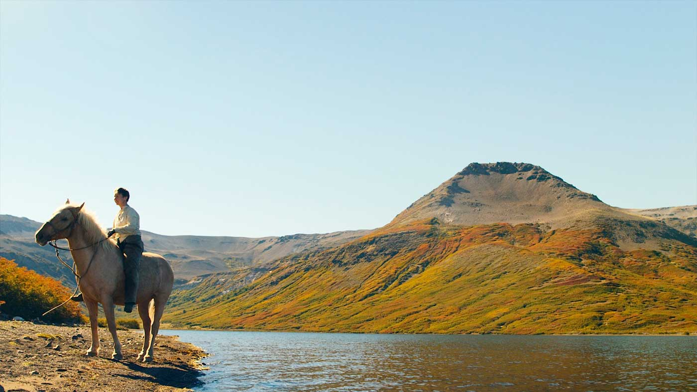 On the shores of an autumnal mountain lagoon, Carly rides bareback.