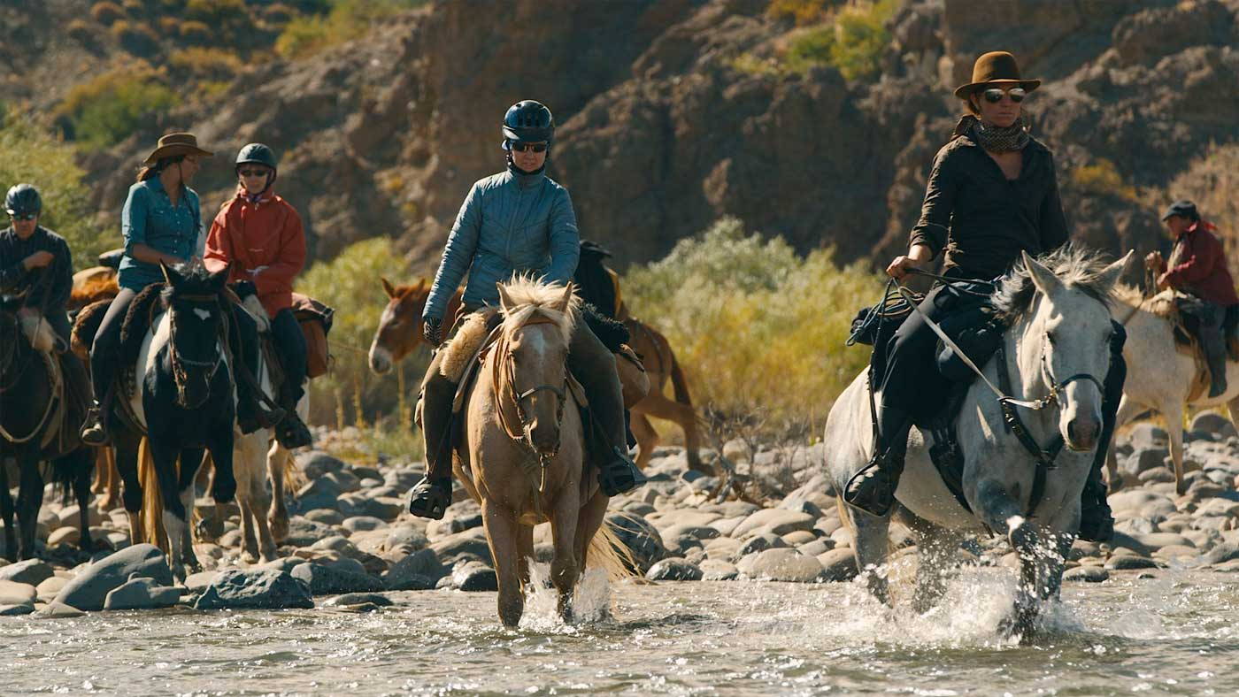 Led by her guide Kyala, Carly and the other riders cross a river.