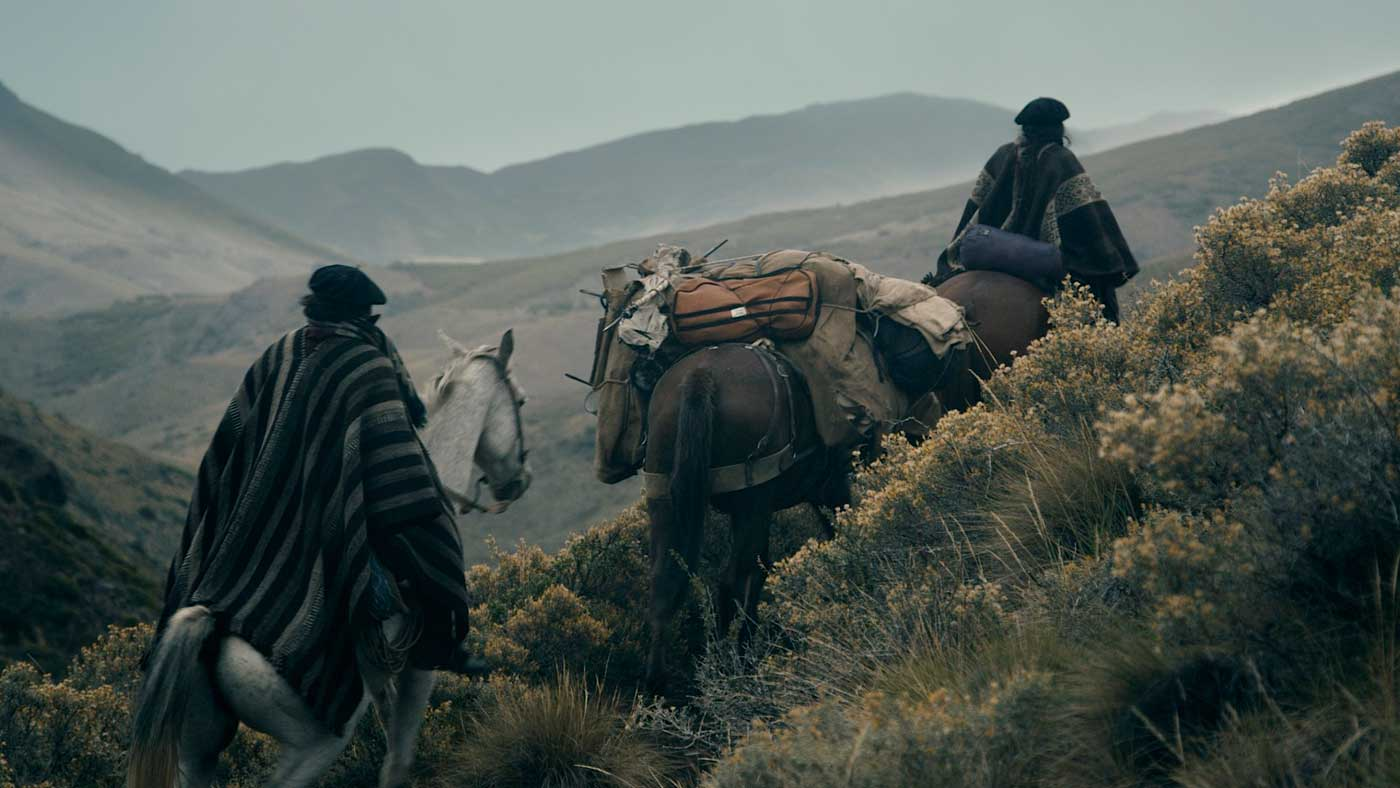 Bundled in their wool ponchos and berets, two gauchos lead the mules into the stormy mountains.
