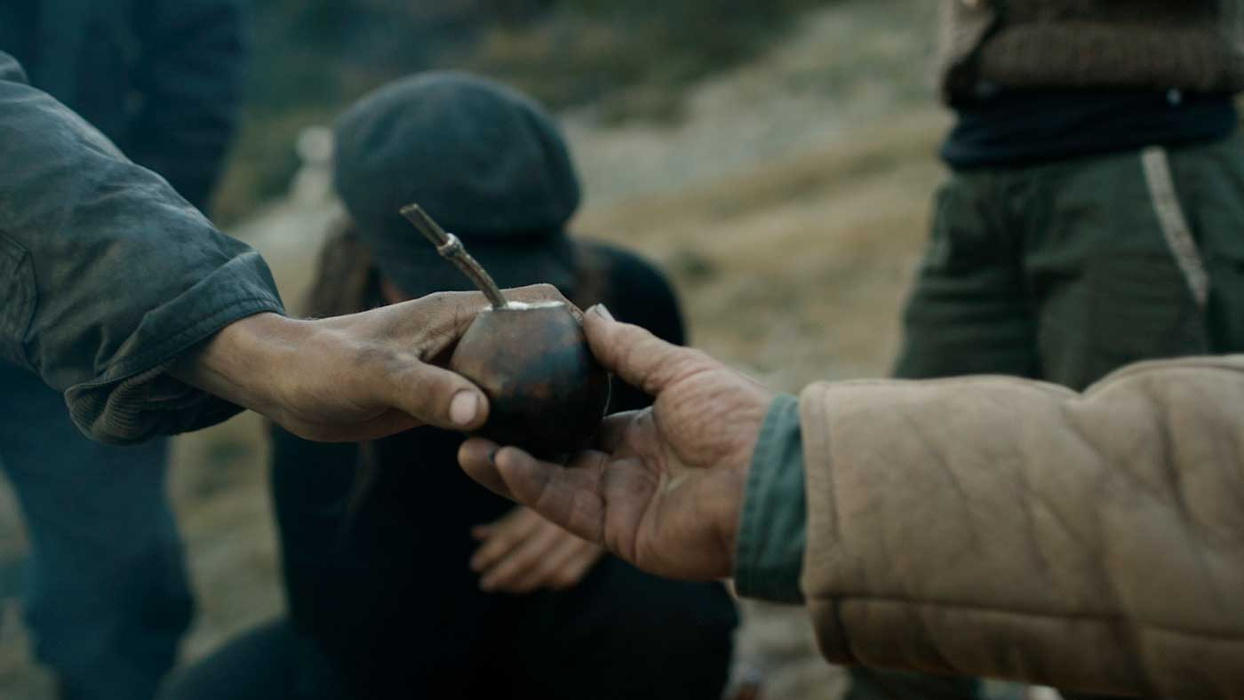 World-weary and weather-worn hands exchange the maté gourd over the campfire.