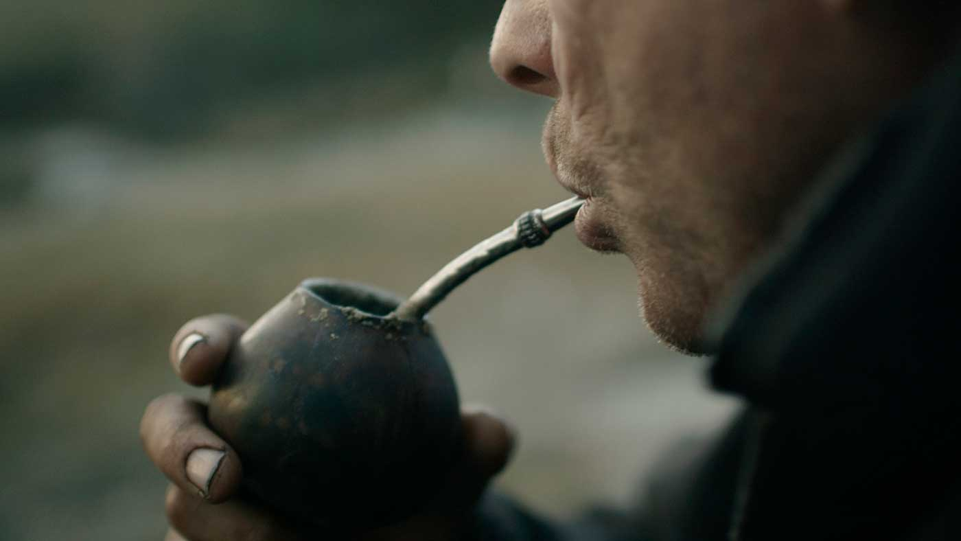 Close-up of Gaucho's mouth as he sips from the maté gourd's bombilla.