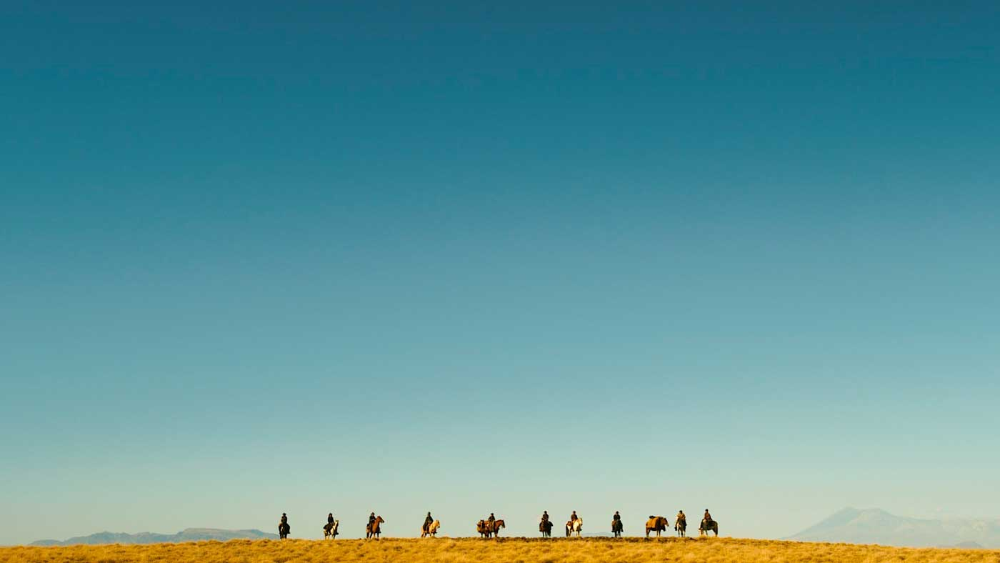 Like a victorious cavalry of heroes, the riders stand side-by-side, silhouetted against a cloudless, cerulean sky.